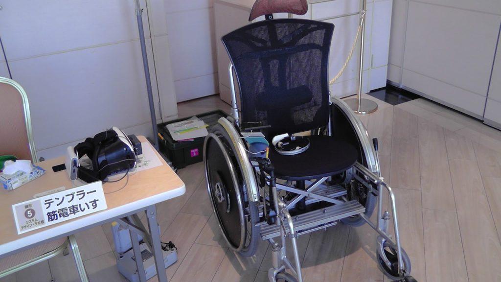 テンプラー筋電車椅子の展示ブースの写真。電動車いすの座席に頭にセットするギアが置かれている