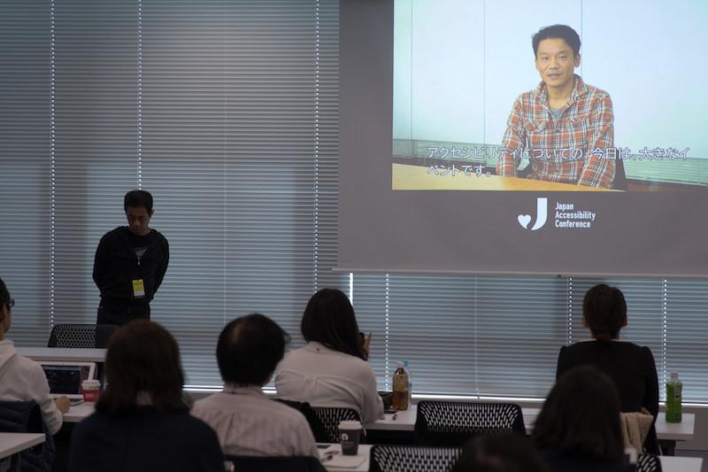 プロジェクタに投影されたビデオ映像を捉えた写真。ビデオでは一人の男性が話している様子が映されている